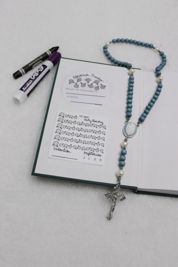 Two dry-erase prayer tracker stickers on inside cover of journal, with dry-erase marker and crayon and Rosary